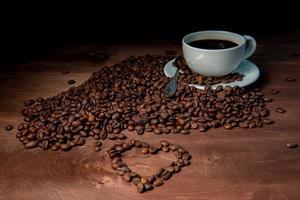 Taza de café con leche y granos de café en el fondo de madera oscura.