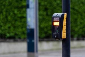 Botón de paso de peatones para peatones con advertencia de luz sobre un fondo desenfocado foto