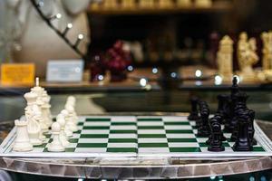 una mesa con un tablero de ajedrez y figuras a un lado foto