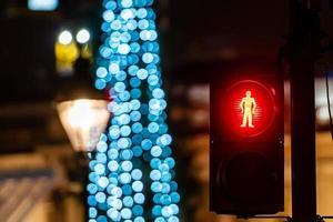 Pedestrian semaphore with green light and defocused Christmas tree lights