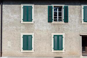 Facade of a stone house with green shutters photo