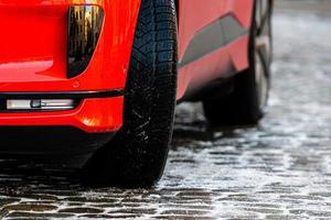 Close-up of a red car with winter tires on an icy pavement photo