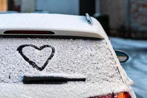 Heart shape on snow-covered car rear window photo