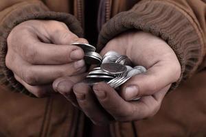 monedas en manos del mendigo foto