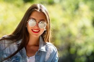 Retrato al aire libre de una mujer joven hermosa, emocional, con gafas de sol foto