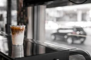 Glass of iced coffee with milk on the table photo