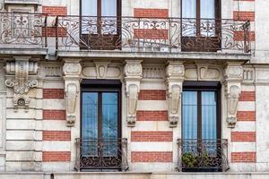 Facade of a historic brick building with metal balconies photo