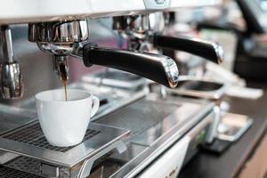 Espresso negro goteando de la cafetera foto