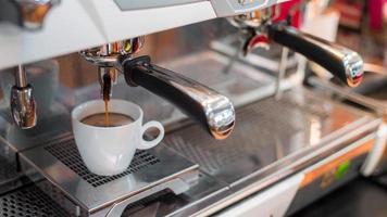 Black espresso coffee dripping from machine photo