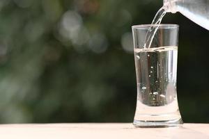 Agua potable mineral en la mesa de madera y agua en vidrio foto