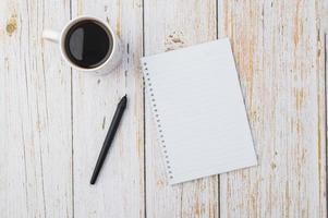 Coffee and a notebook with a pen on a wooden desk photo