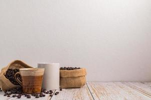 Coffee mugs and bags of coffee beans on a wooden table photo