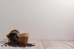A coffee mug and a bag of coffee beans on a wooden table photo