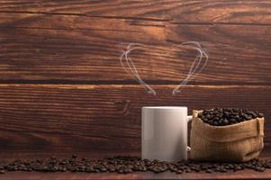 A coffee mug making heart-shaped steam with a bag of coffee beans on a wooden table photo