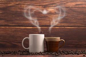 Coffee mugs making heart-shaped steam on a wooden table photo