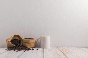 A coffee mug and bags of coffee beans on a wooden table photo