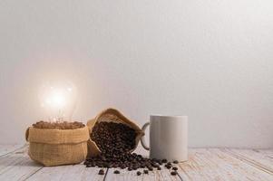 una taza de café con bolsas de granos de café y una bombilla que emite energía sobre una mesa de madera