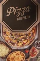 Pizza with mozzarella, onion, pepperoni, black olive, green peppers, nachos and oregano in a delivery box photo