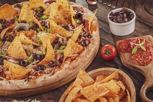 Pizza with mozzarella, onion, pepperoni, black olive, green peppers, nachos and oregano photo