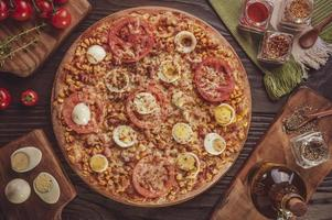 Brazilian pizza with mozzarella, corn, bacon, eggs, tomato and oregano