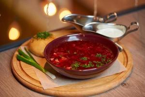 A Ukrainian borsch with a pampushka, onion, and sour cream on a wooden tray