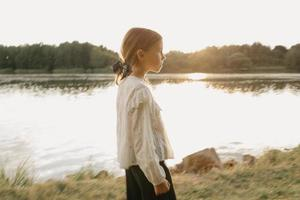 A blurred portrait of a young girl who is watching straight and walking on the coast photo
