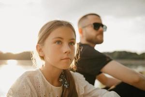A close portrait of a young girl who is posing with her father with a beard and sunglasses on the coast