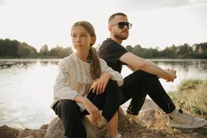 A young girl is posing on stones with her father with a beard and sunglasses on the coast of the lake
