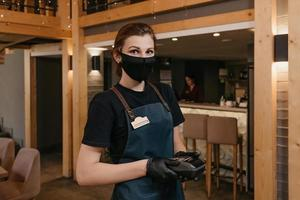 A waitress who wears an apron, a black medical face mask, and disposable medical gloves holds a wireless payment terminal in a restaurant photo