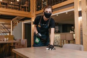 una amable camarera que usa una mascarilla médica negra y guantes médicos desechables sostiene una botella con desinfectante y limpia las mesas con un trapo en un restaurante foto