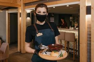 A waitress who wears a black face mask and disposable gloves serves clients in a cafe photo