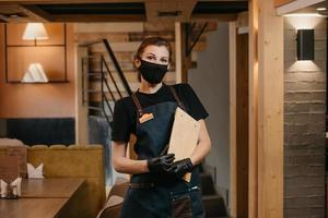 A waitress in black disposable medical gloves wears a medical face mask holding a wooden menu in a restaurant photo