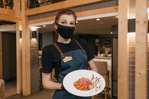 A stylish waitress who wears a black face mask and disposable gloves is holding a mint and dolendwitz salad in a restaurant photo