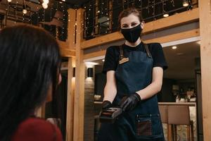 A waitress who wears a medical face mask and disposable medical gloves is handing a wireless payment terminal to a female client in a restaurant photo