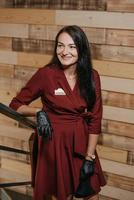 A laughing female restaurant manager in black disposable gloves posing in a coffee shop photo