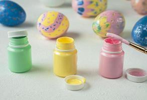 Abrir latas de pintura para pintar huevos de pascua sobre un fondo blanco. foto
