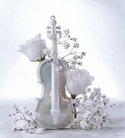 White artificial violin and white flower buds on a white background