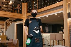 A waitress wears a medical face mask and black disposable medical gloves holding a bottle with sanitizer and a rag to clean tables photo