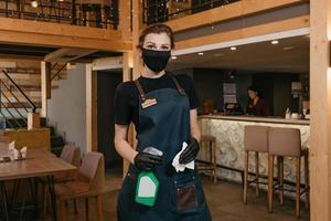 A waitress in a medical face mask is holding a bottle with sanitizer and a rag photo