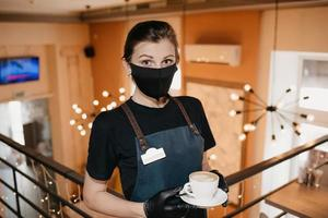 A waitress wears a black face mask and disposable gloves is serving a cup of coffee in a restaurant photo