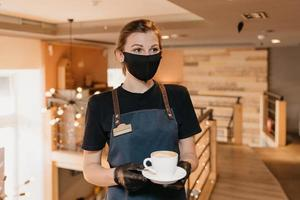 A barista is waiting for clients in a cafe