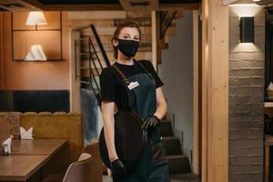 A waitress wears a medical face mask and black disposable medical gloves posing with a plastic tray in a restaurant photo