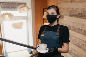 Waitress who wears a face mask and disposable gloves is serving a cup of coffee photo
