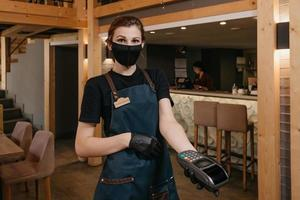 A waitress wears a medical face mask and disposable medical gloves handing a wireless payment terminal to a female client photo