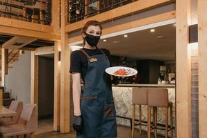 A waitress who wears a black face mask is holding a mint and dolendwitz salad photo