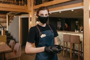 A female restaurant manager wears a black face mask and disposable gloves holding a payment terminal in a restaurant photo