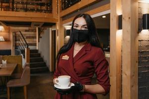 A female restaurant manager wears a black face mask and disposable gloves holding a cup of coffee in a restaurant photo
