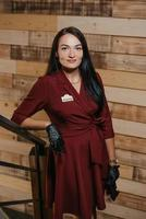 A female restaurant manager in black disposable gloves posing in a coffee shop photo
