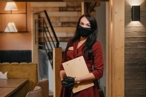 A female restaurant manager in black disposable medical gloves wears a medical face mask is posing holding a wooden menu in a restaurant photo