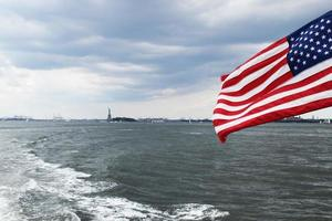 American flag with Statue of Liberty in the background photo